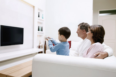 Man and woman watching television, boy using remote control Stock Photo