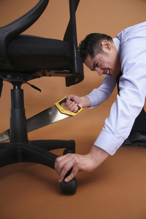 french ethnicity: Businessman cutting chair with saw
