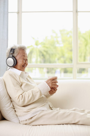 Senior woman with headphones holding a cup of coffee photo