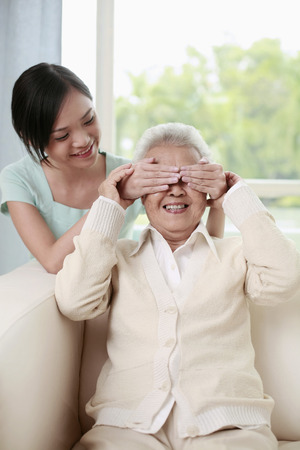 and guessing: Woman covering senior womans eyes