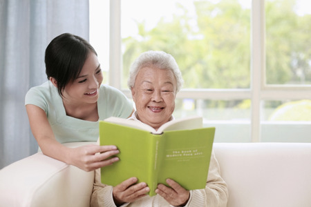 Senior woman and woman reading book together Stock Photo