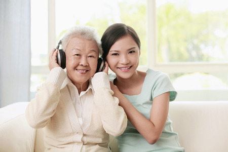 Senior woman listening to music on the headphones, woman posing beside her photo