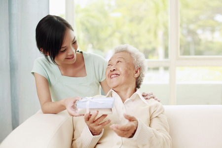 Woman giving senior woman a box of gift