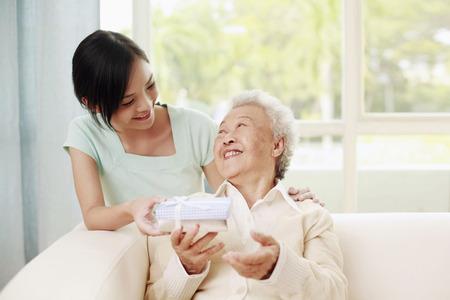 Woman giving senior woman a box of gift
