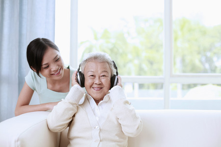 Senior woman listening to music on the headphones, woman looking at her Stock Photo