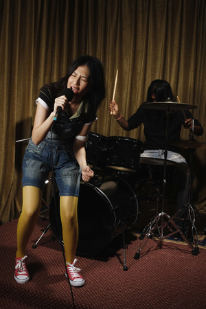 Young woman singing, man playing drums in the background photo