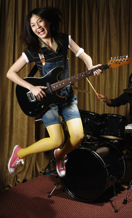 Young woman jumping while playing guitar, man playing drums in the background photo