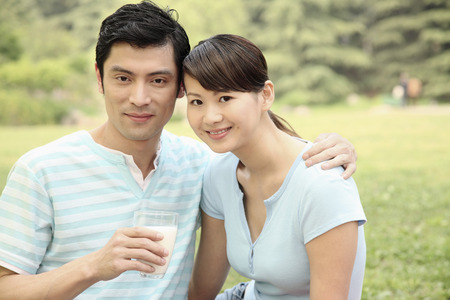 Man holding a glass of milk with the hand on woman's shoulder photo
