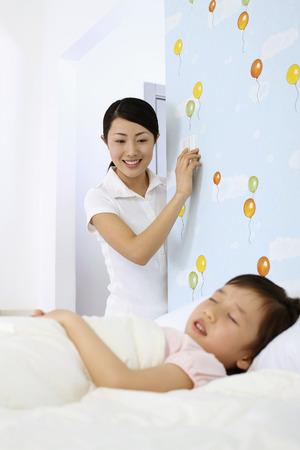 eyes closing: Woman switching off lights while girl is sleeping