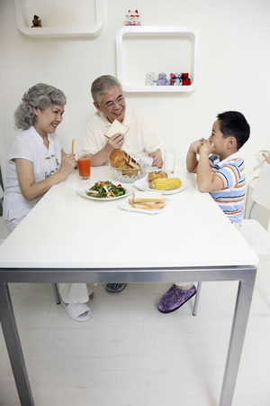 Boy having breakfast with senior man and senior woman photo