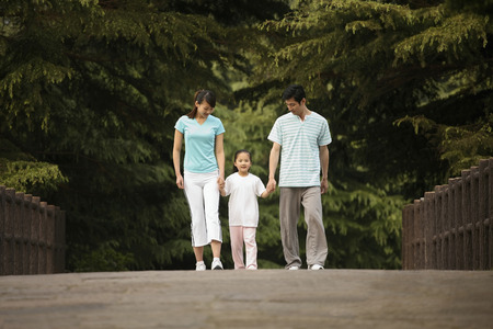 Girl holding hands with parents while walking in the park photo