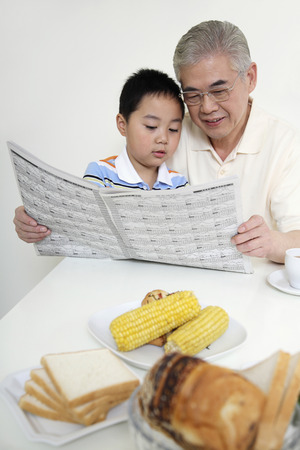 Senior man and boy reading newspaper together Stock Photo - 26226590