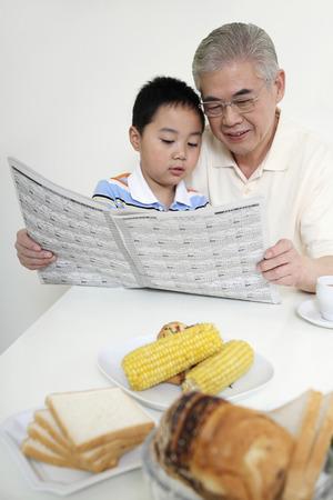 Senior man and boy reading newspaper together photo