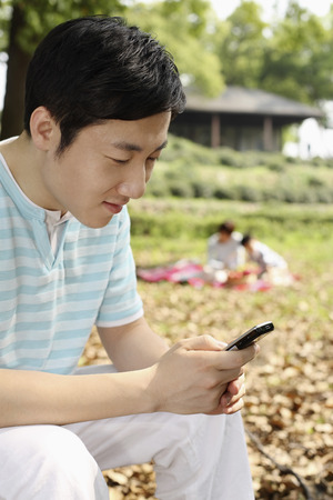 Man text messaging on the cell phone, boy and woman having a picnic in the background photo