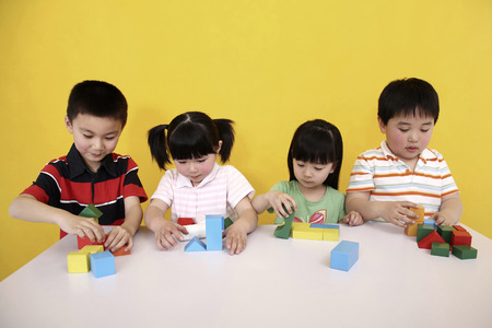 four person only: Children playing with building blocks
