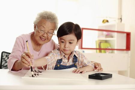 Senior woman teaching boy calligraphy Stock Photo