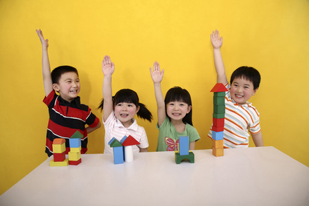 Children playing with building blocks, raising their hands
