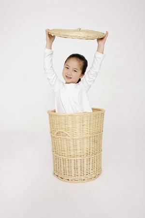 Girl hiding inside laundry basket photo