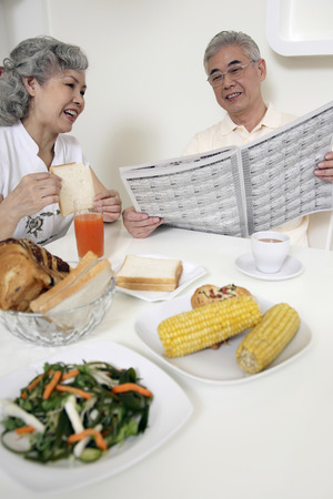Senior man and senior woman reading newspaper while having breakfast together photo