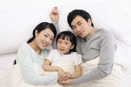 Family lying in bed together, smiling