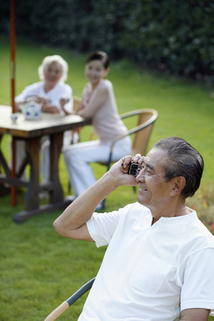 Senior man talking on the phone, senior woman and woman having tea in the background