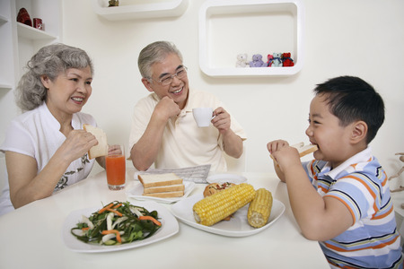 Boy eating bread, senior man and senior woman watching photo