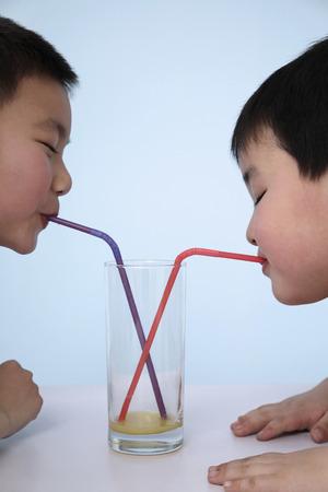 Boys sharing a glass of orange juice photo