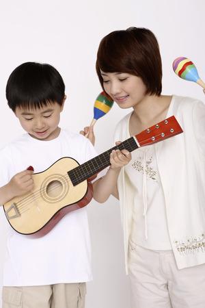 Boy playing guitar while woman shaking maracas photo