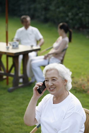 Senior woman talking on the phone, woman having tea with senior man in the background photo
