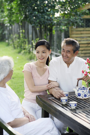 Woman having tea with senior couple in the park photo