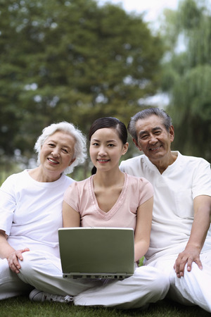 Woman with laptop posing with senior couple in the park photo