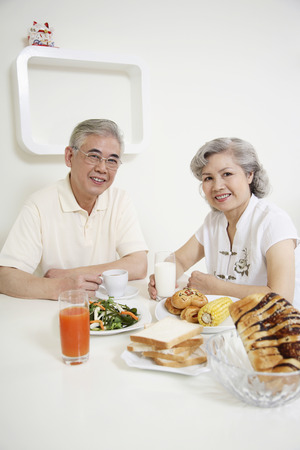 Senior man and senior woman having breakfast together Stock Photo