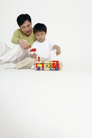 Man and boy playing with educational toy photo