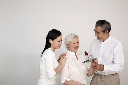 Senior man giving senior woman a stalk of rose, woman smiling while watching photo