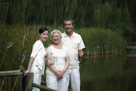 Senior man fishing on a dock, senior woman and woman posing beside him photo
