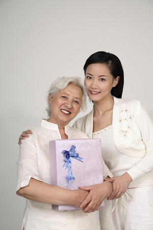 Senior woman holding a gift, woman posing with her photo