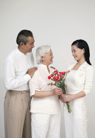 Woman giving senior woman a bouquet of flowers, senior man smiling while watching photo