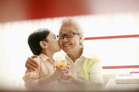 Boy handing senior woman a glass of orange juice and giving her a kiss on her cheek Stock Photo - 26201817