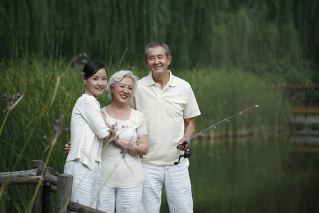 three generations: Senior man fishing on a dock, senior woman and woman posing beside him