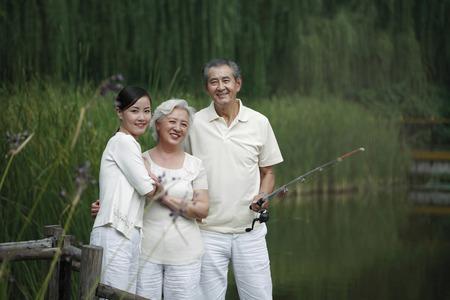Senior man fishing on a dock, senior woman and woman posing beside him