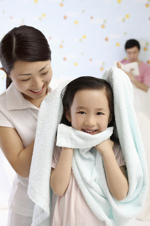 Woman drying girls hair with towel