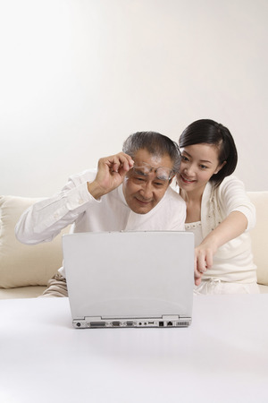 Woman teaching senior man how to use laptop photo