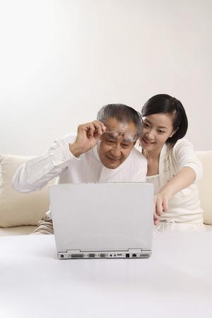 Woman teaching senior man how to use laptop Stock Photo - 26203539