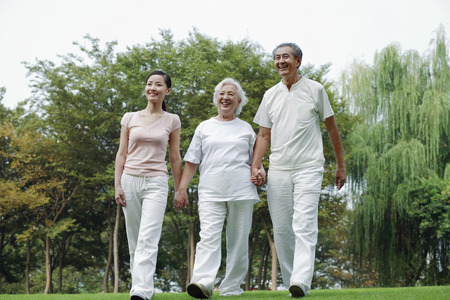 holding hands while walking: Woman together with senior couple holding hands while walking in the park