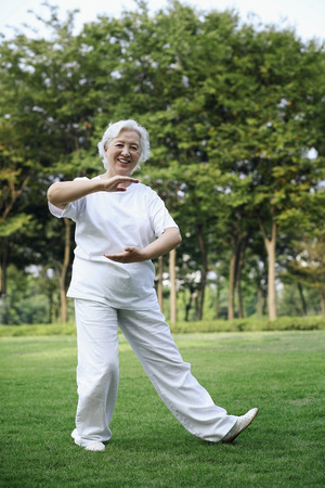 Senior woman practising tai chi in the park