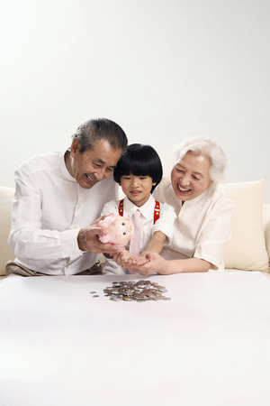 Senior couple helping boy to count coins in his piggy bank photo