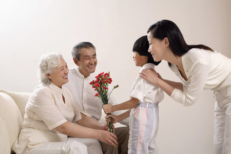 Boy giving a bouquet of flowers to senior woman, woman and senior man watching Stock Photo - 26203434