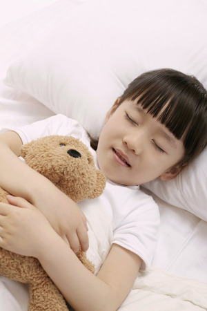 Girl sleeping and hugging soft toy photo