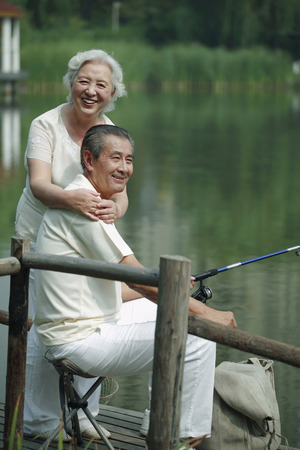 Senior man fishing on a dock, senior woman posing beside him photo