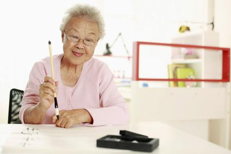 Senior woman writing calligraphy